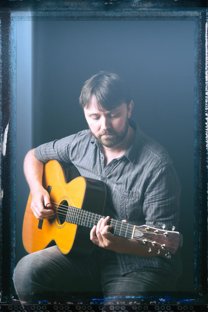 Donal Clancy sitting playing a guitar