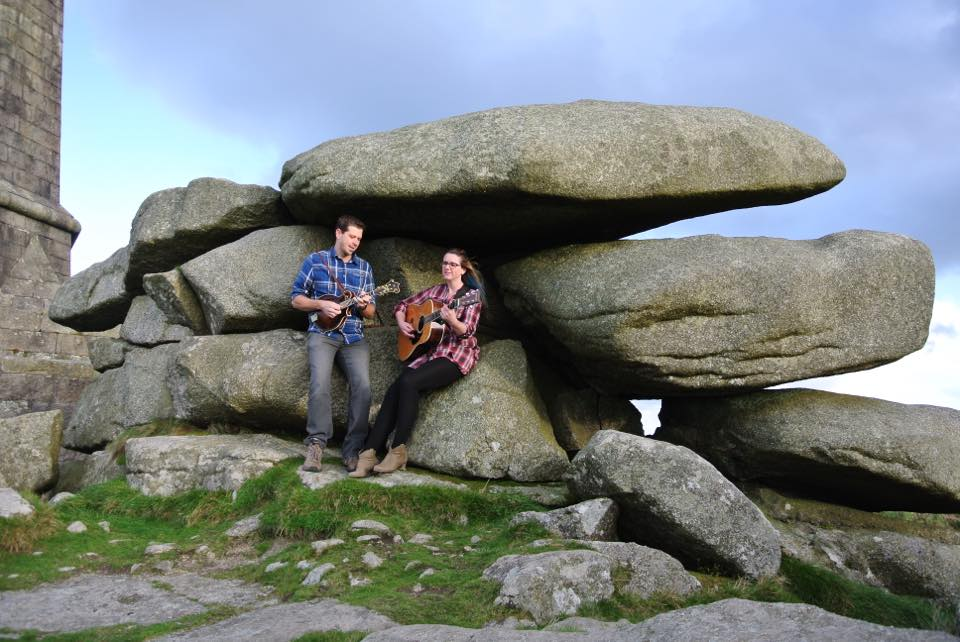 Playing guitar & mandolin at Carn Brea with a granite tor backdrop