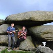man and woman playing instruments while sitting on granite rock